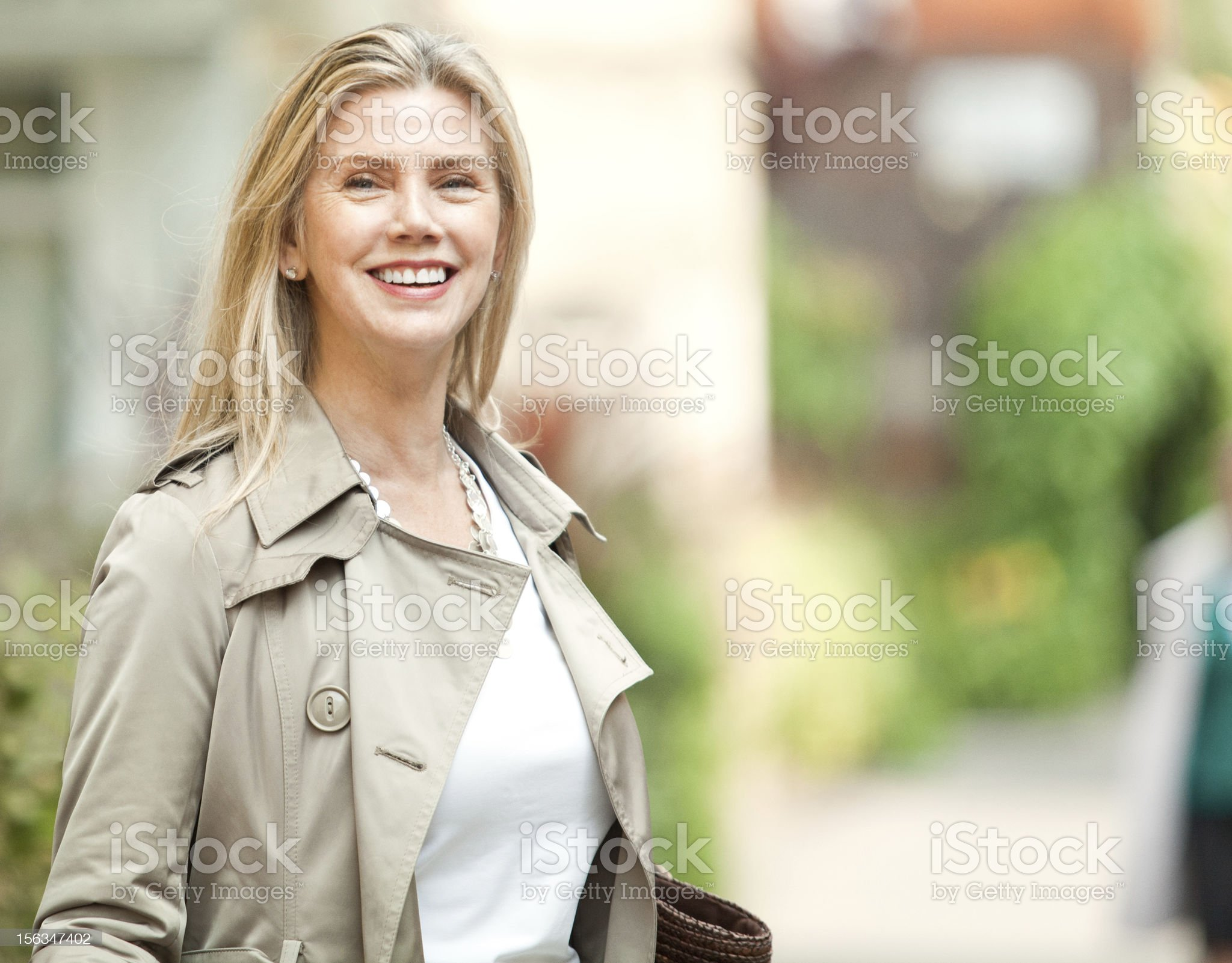 Beautiful smiling mature woman on the street with a bag. royalty-free stock photo