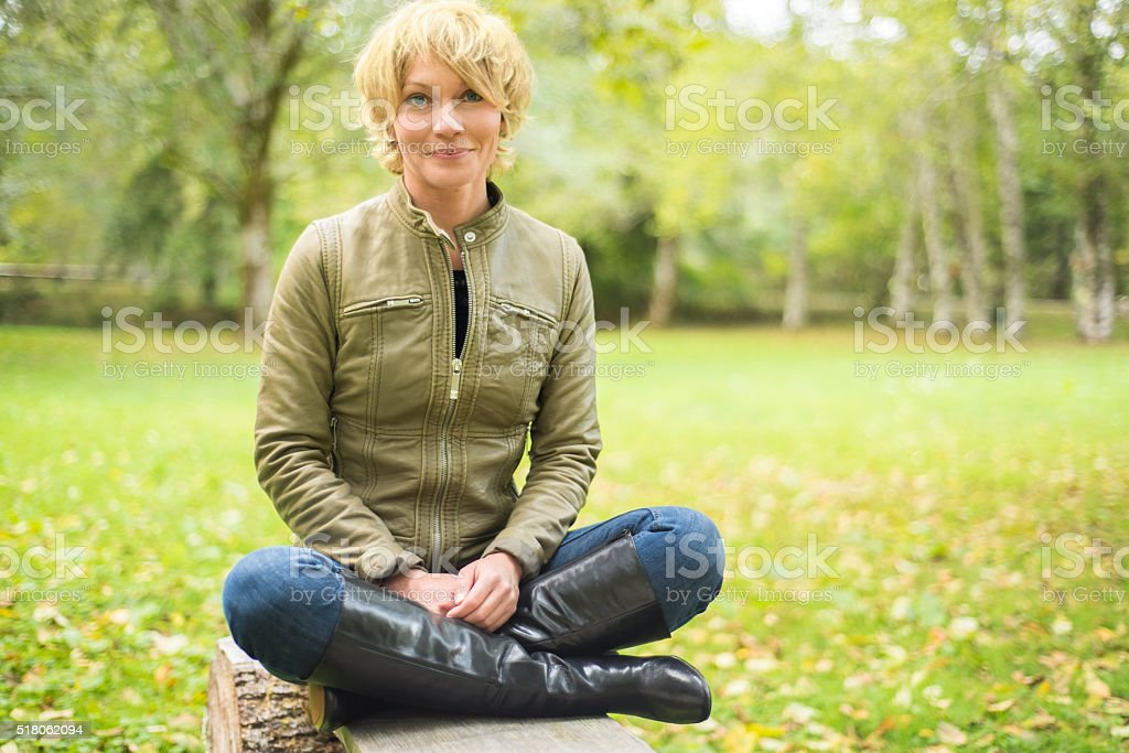 Beautiful, smiling, mid 30's Woman sitting cross-legged. stock photo