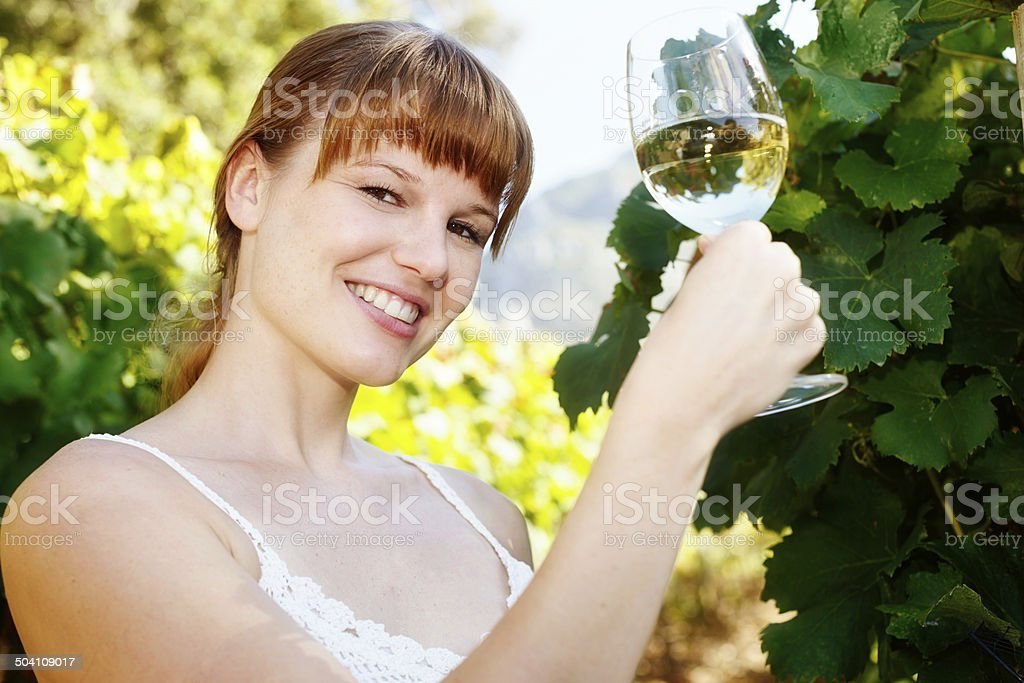 Beautiful, smiling  redhead holds up glass of white wine, toasting royalty-free stock photo