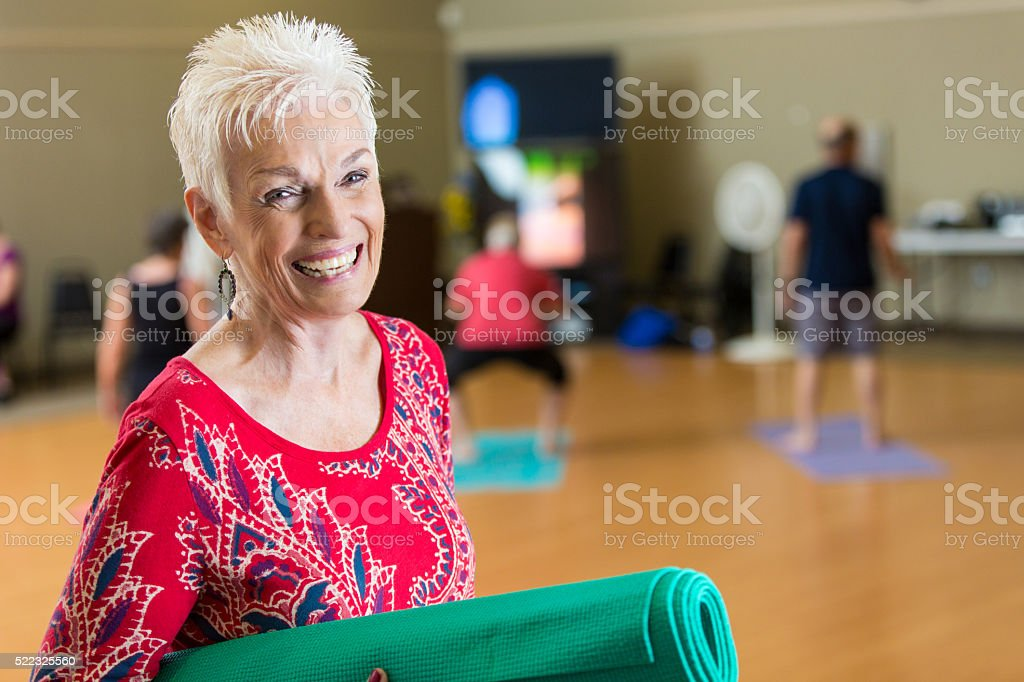 Beautiful smiling senior woman before yoga class stock photo