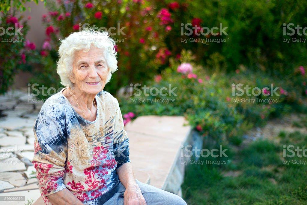 Beautiful smiling senior woman sitting in garden stock photo