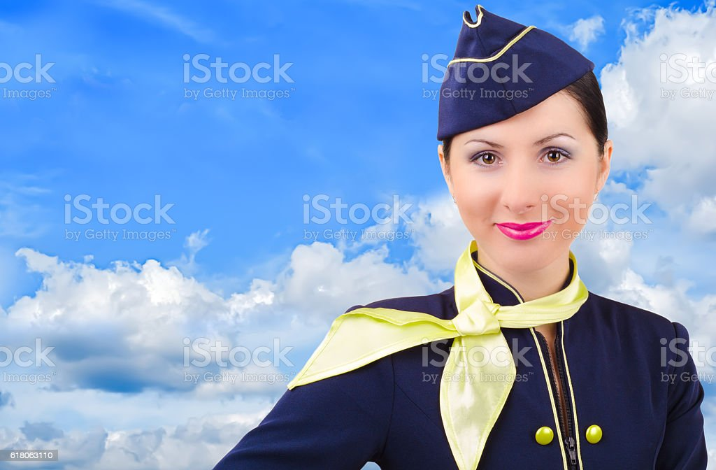 Beautiful smiling stewardess on a background cloudy sky stock photo