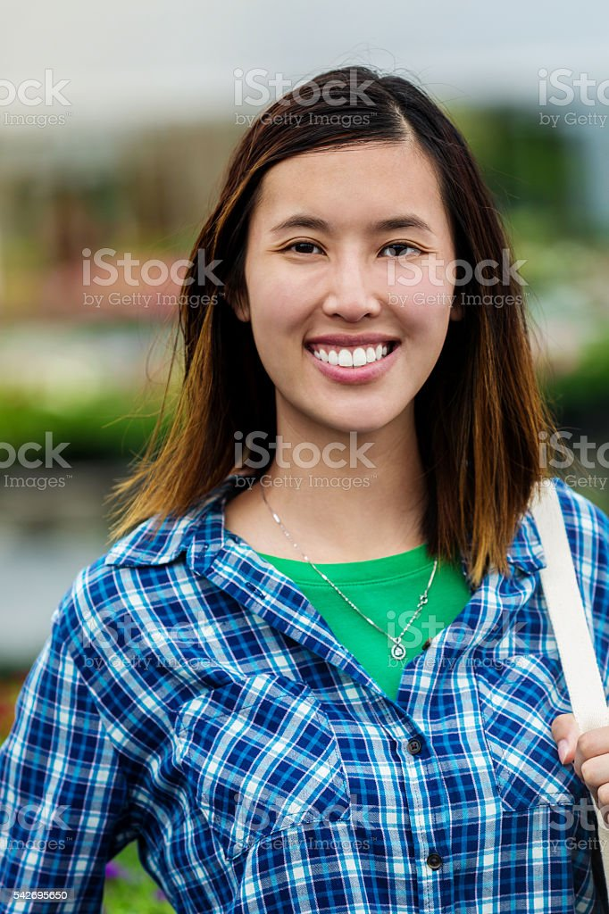 Beautiful smiling Vietnamese Woman in a blue plaid shirt stock photo