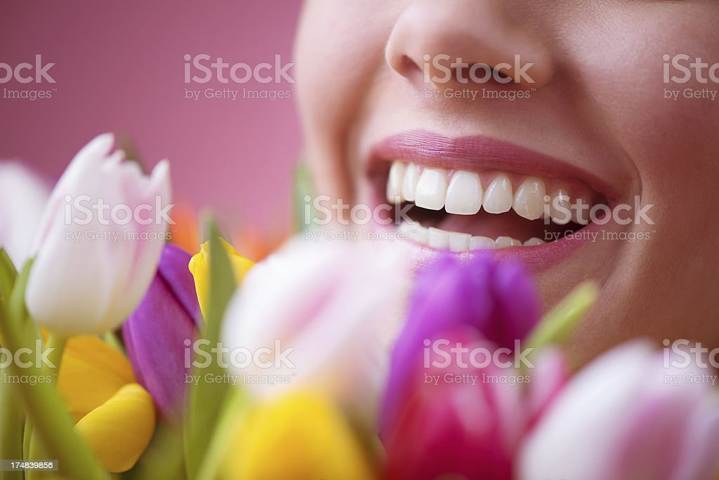 Beautiful Smiling Woman Behind Tulips royalty-free stock photo
