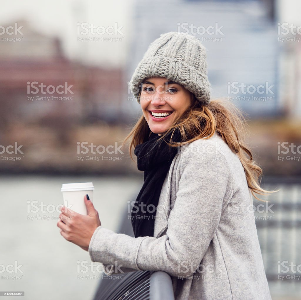 Beautiful smiling woman drinking coffee from paper cup outdoors stock photo