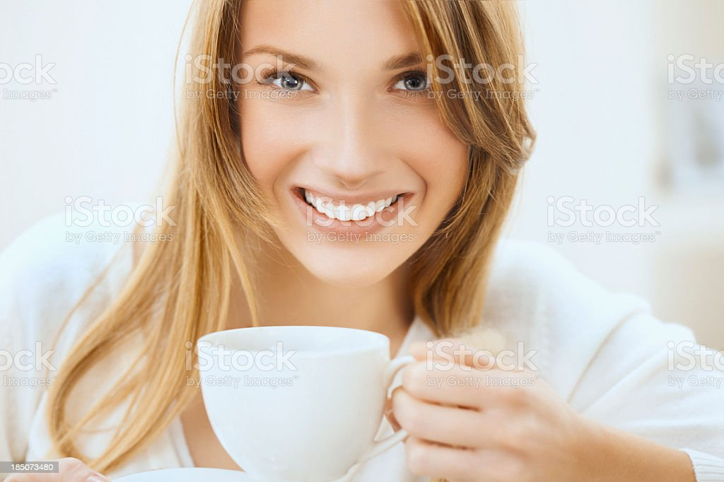 Beautiful, smiling woman holding a cup of tea or coffee royalty-free stock photo