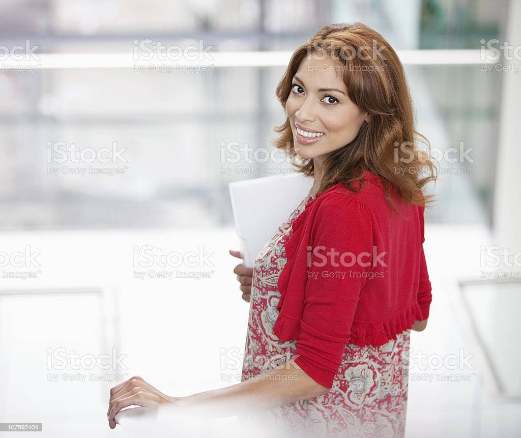 Beautiful smiling woman holding document on staircase at office royalty-free stock photo