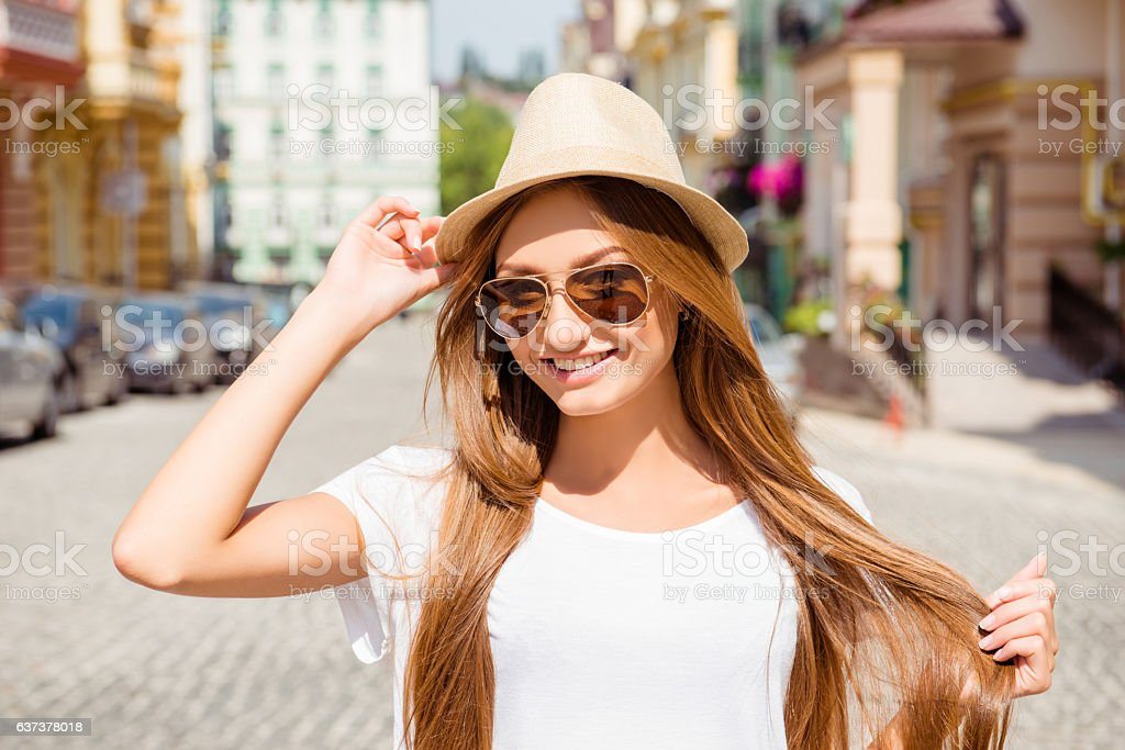 beautiful smiling woman in hat and glasses walking stock photo