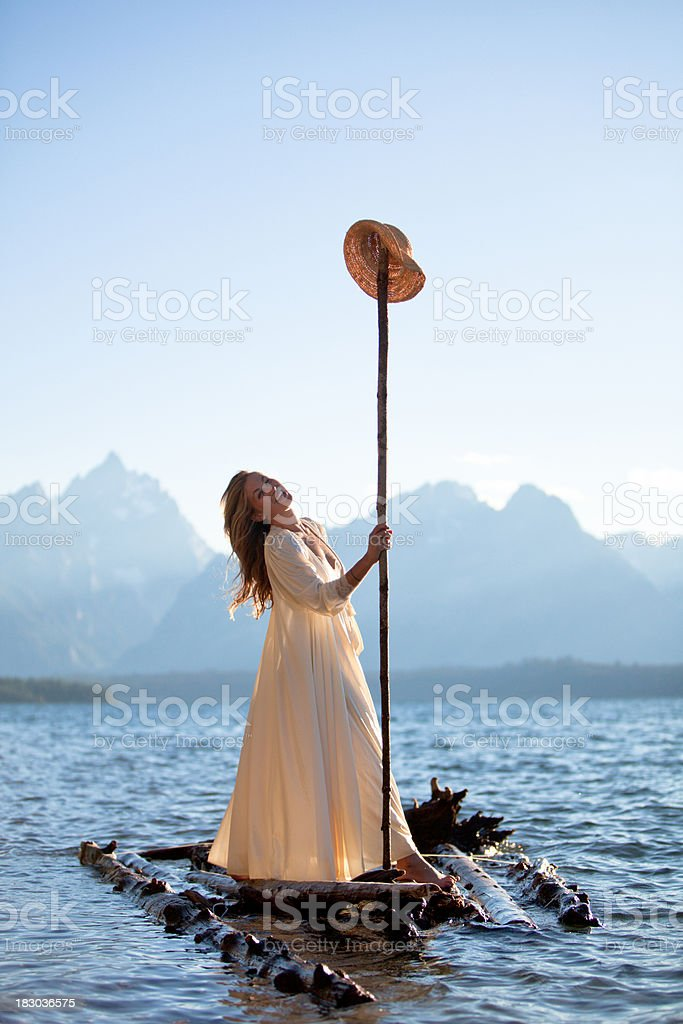 Beautiful smiling woman on a wooden raft royalty-free stock photo