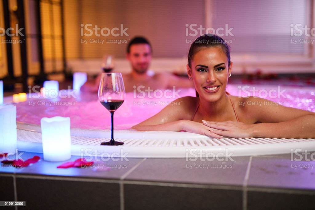 Beautiful smiling woman relaxing in jacuzzi at health spa. stock photo