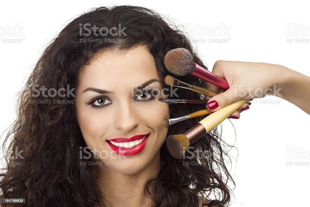 Beautiful smiling woman with make-up brushes near her face royalty-free stock photo