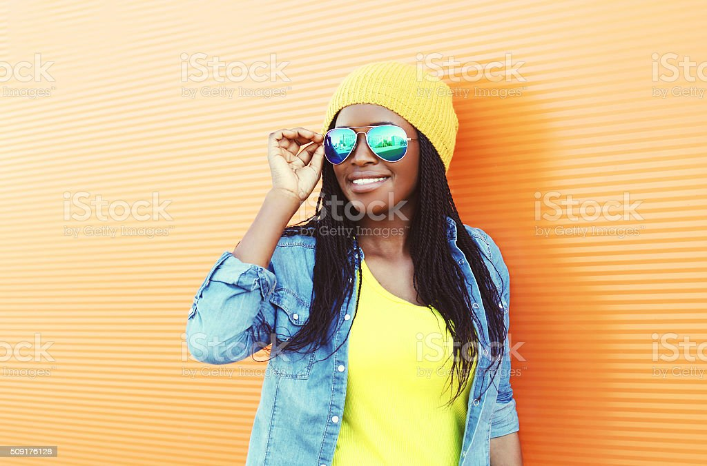 Beautiful smiling young african woman wearing a sunglasses stock photo
