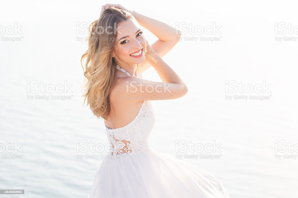 Beautiful smiling young bride girl over the sea view stock photo