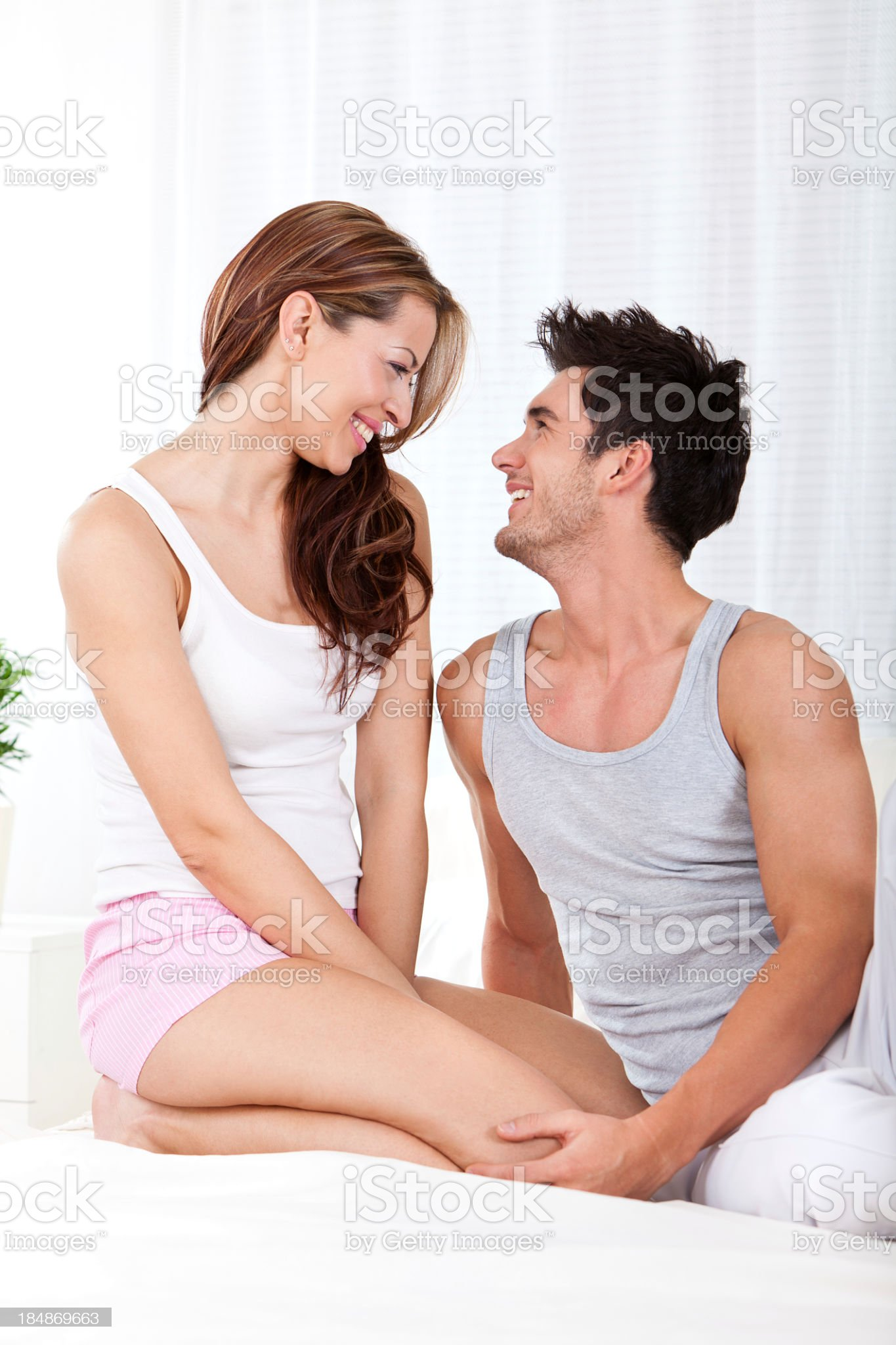 Beautiful smiling young couple sitting on bed royalty-free stock photo