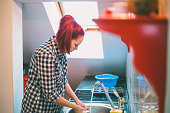 Beautiful smiling young woman doing the washing up in kitchen