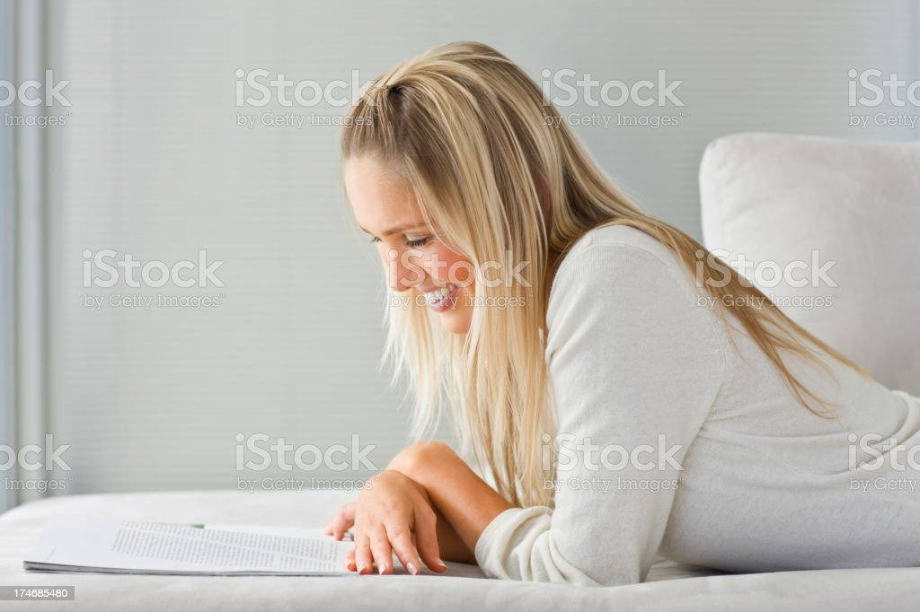 Beautiful smiling young woman reading a book royalty-free stock photo