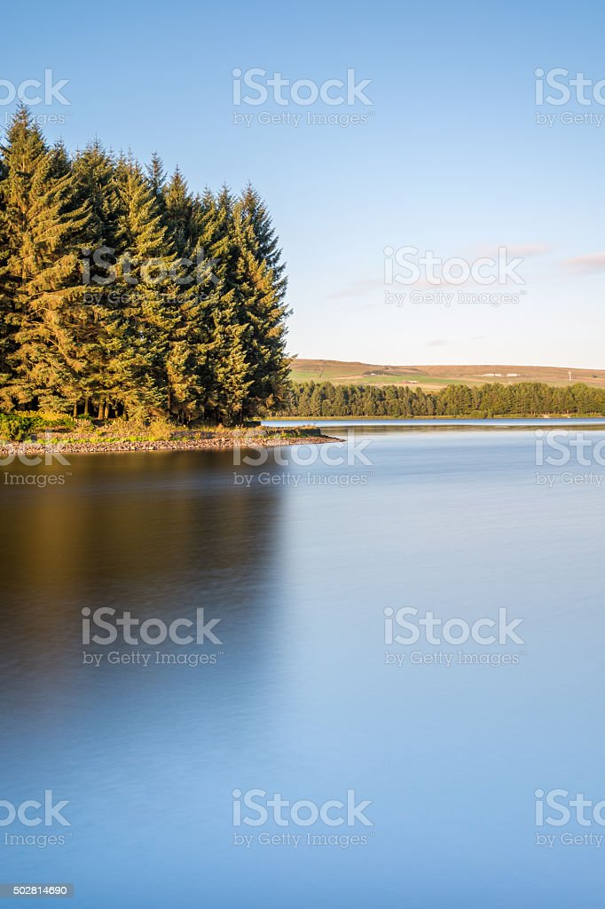 Beautiful Smooth Water At Lake With Golden Light On Trees. stock photo