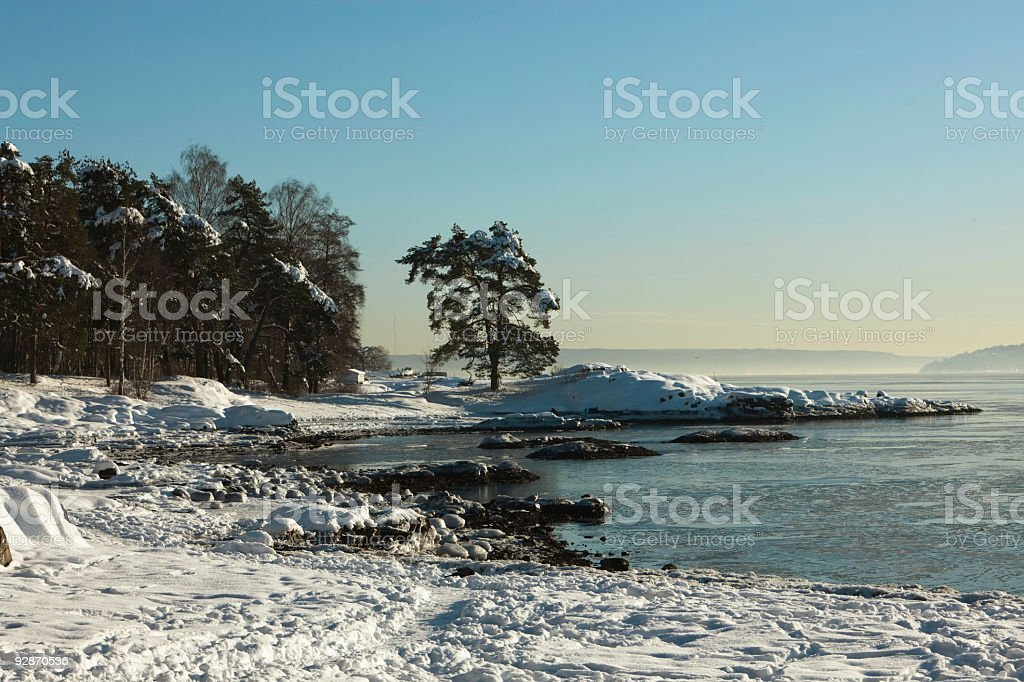 Beautiful snowy landscape by the sea at sunset. stock photo