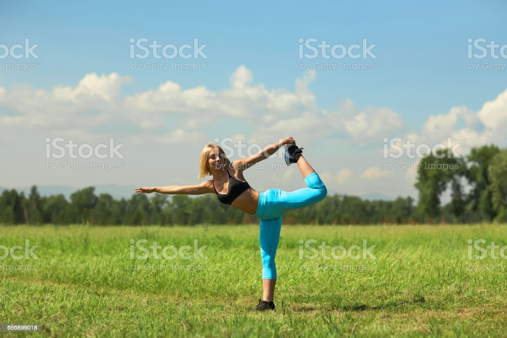 Beautiful sport woman doing stretching fitness exercise in city park at green grass. Yoga postures stock photo