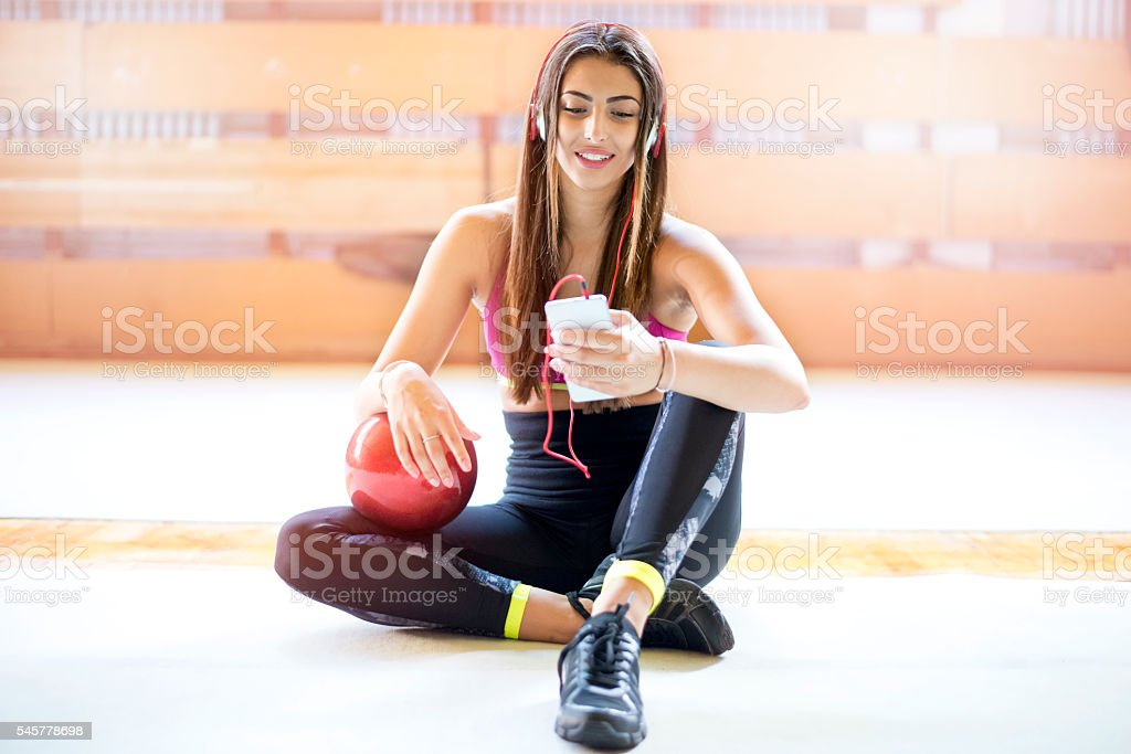 Beautiful sports woman using smartphone in fitness gym stock photo