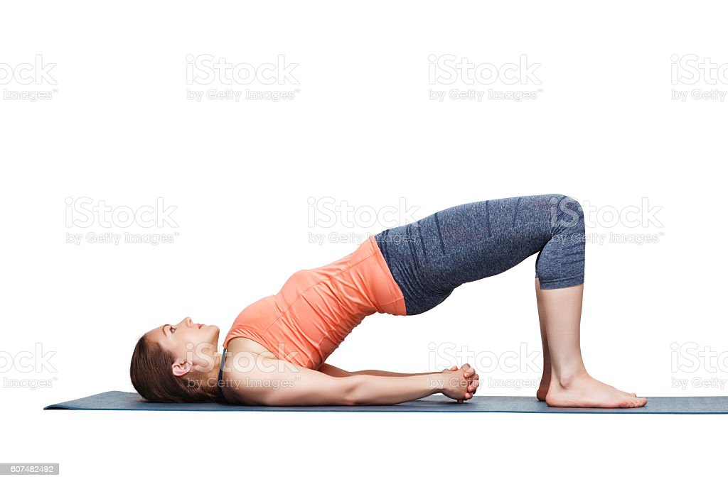 Beautiful sporty fit yogi girl practices yoga asana setu bandhas stock photo
