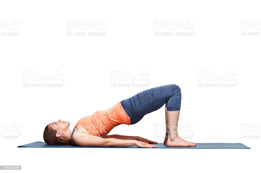 Beautiful sporty fit yogi girl practices yoga asana setu bandhasana stock photo