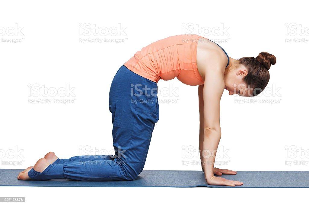 Beautiful sporty fit yogini woman practices yoga asana marjariasana stock photo