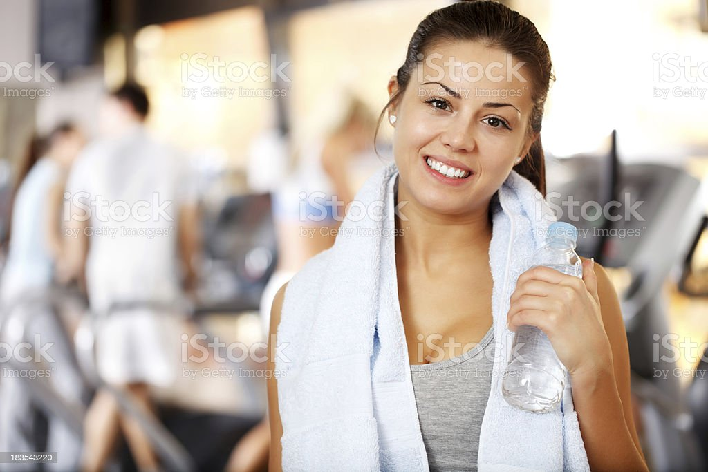 Beautiful sporty girl is smiling and resting in a gym. royalty-free stock photo