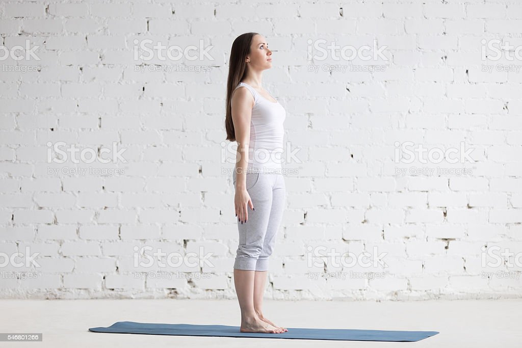 Beautiful sporty young woman doing Tadasana pose in white loft stock photo