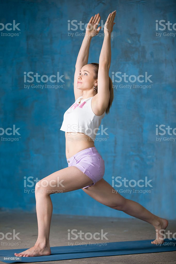 Beautiful sporty young woman Doing Virabhadrasana 1 pose stock photo