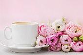 Beautiful spring Ranunculus flowers and cup of coffee. Holiday concept.
