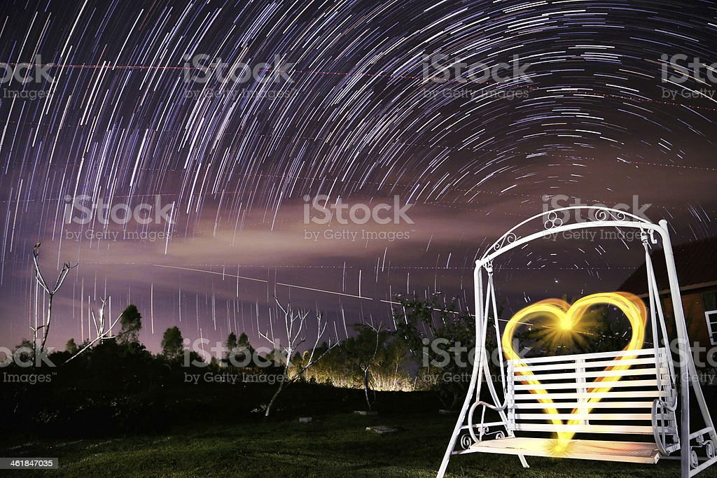 Beautiful star trail during the night and Garden swing stock photo