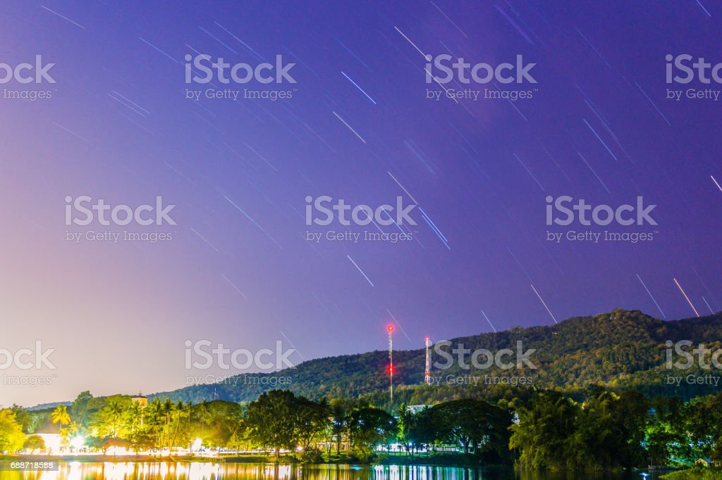 Beautiful star trails in the sky at chiangmai university thailand and suthep mountain stock photo