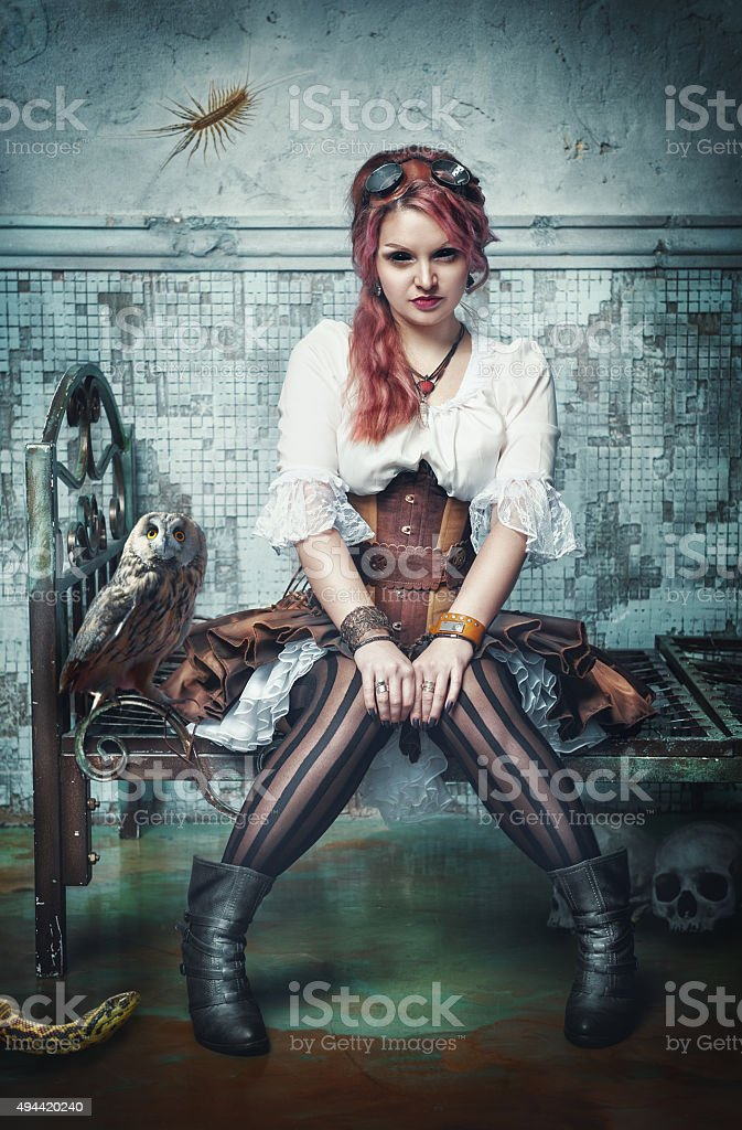Beautiful steampunk witch in the abandoned room stock photo