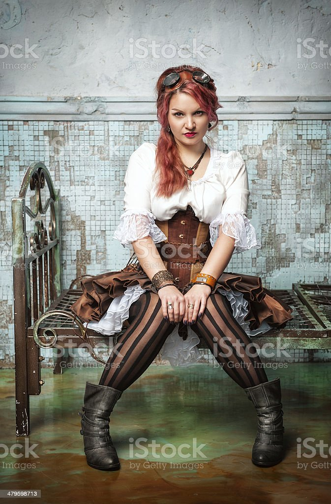 Beautiful steampunk woman on the metal bed stock photo