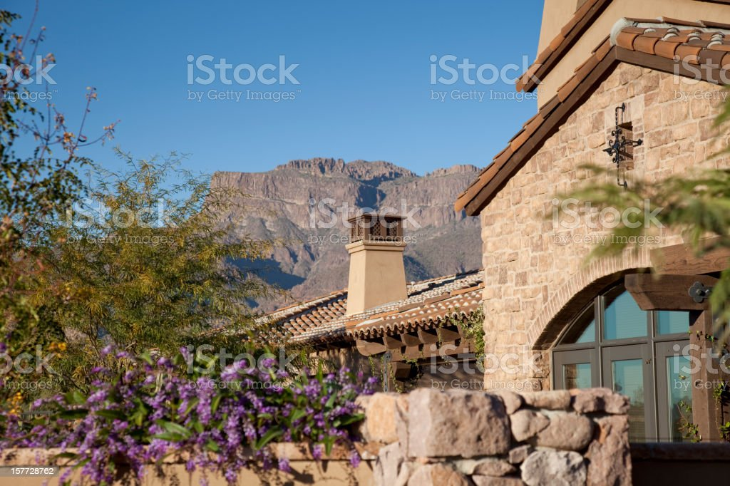 Beautiful stone built home in the shadow of a stone mountain stock photo