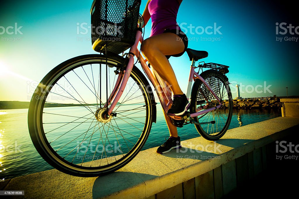 Beautiful streight woman with bicycle on sunset near a sea stock photo