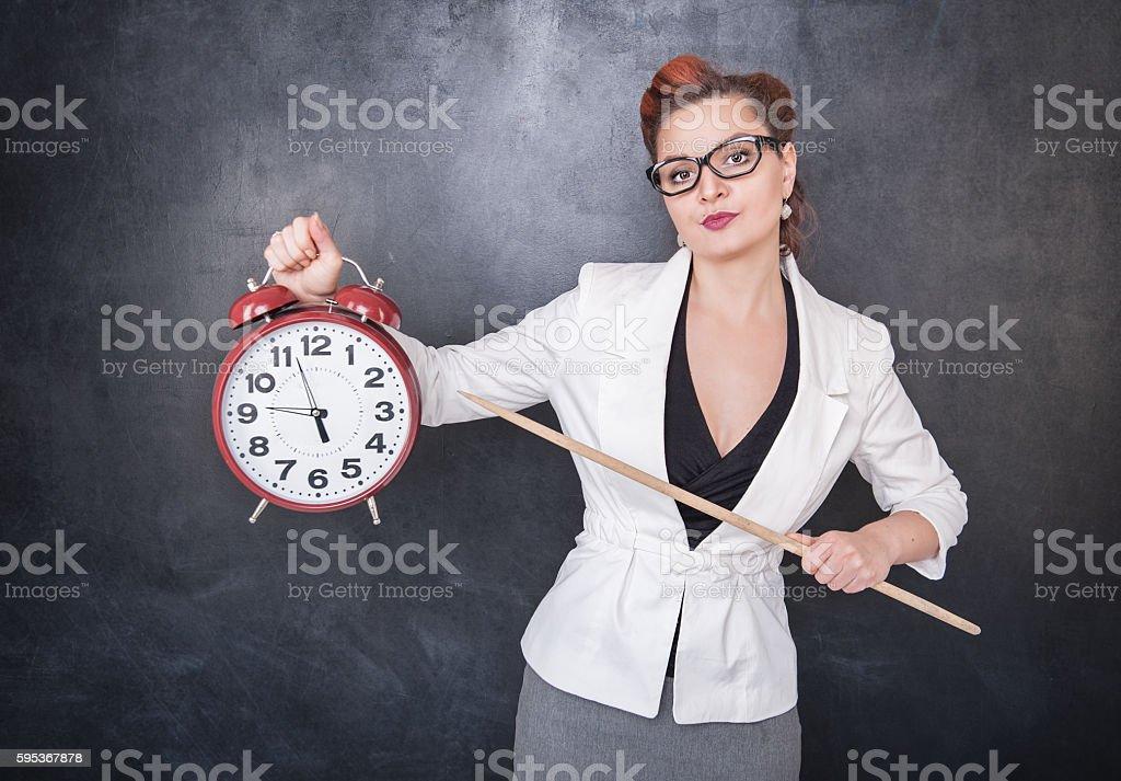Beautiful strict teacher with clock stock photo