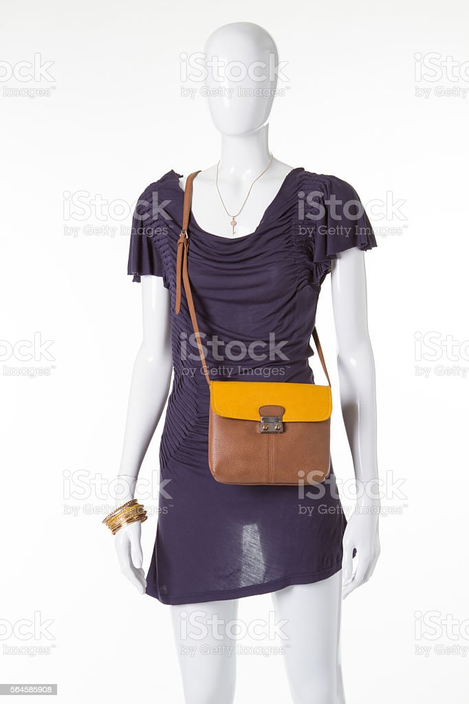 Beautiful stylish dress with a purse on a white mannequin. stock photo