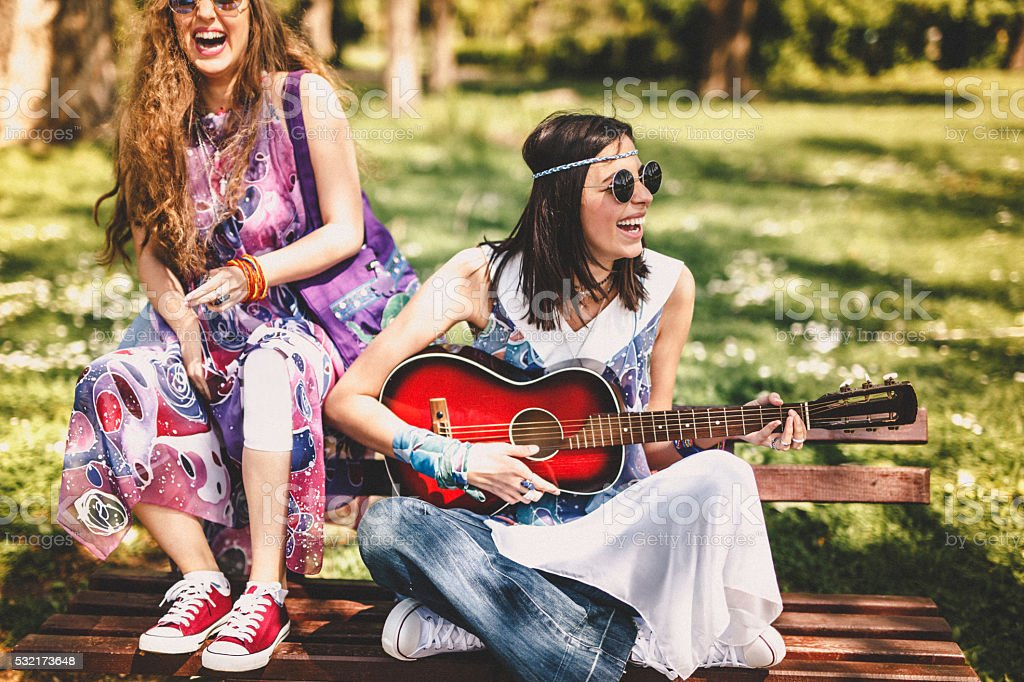 Beautiful stylish friends playing guitar stock photo