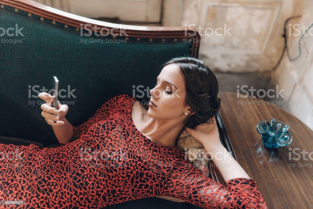 beautiful stylish young cuban woman checking mobile on sofa stock photo