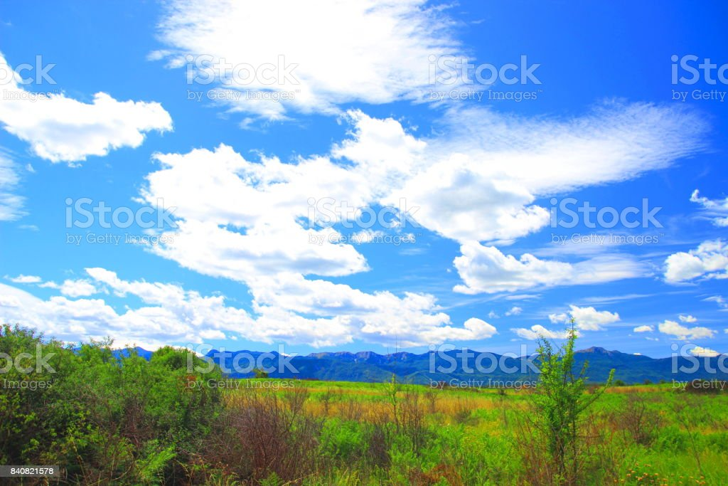 Beautiful summer day in nature, blue sky with white clouds, high mountains in background stock photo