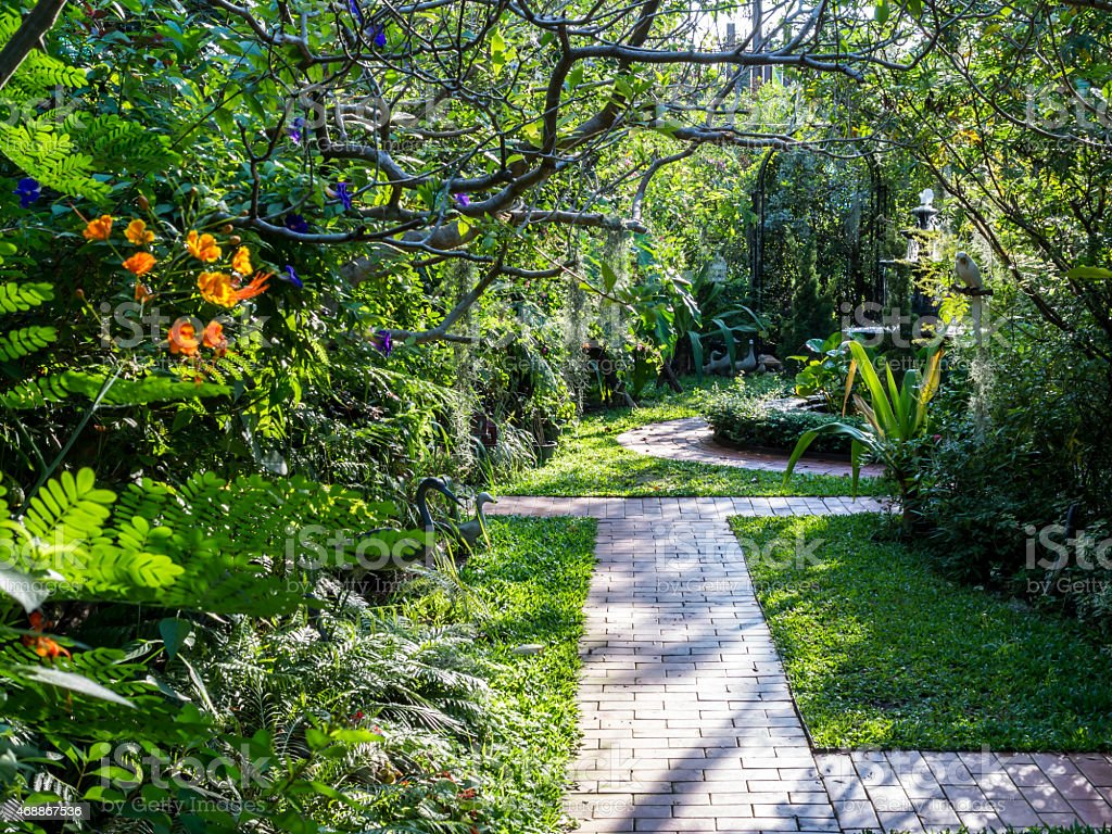 Beautiful summer English formal garden courtyard with pathway stock photo