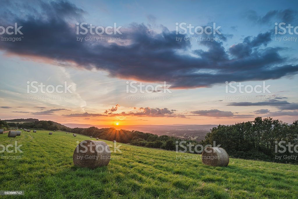Beautiful Summer vibrant sunset over countryside landscape of fi stock photo