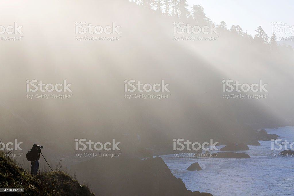 Beautiful Sunlight Rays on Rocky Coastline with Landscape Photographer, Copyspace royalty-free stock photo