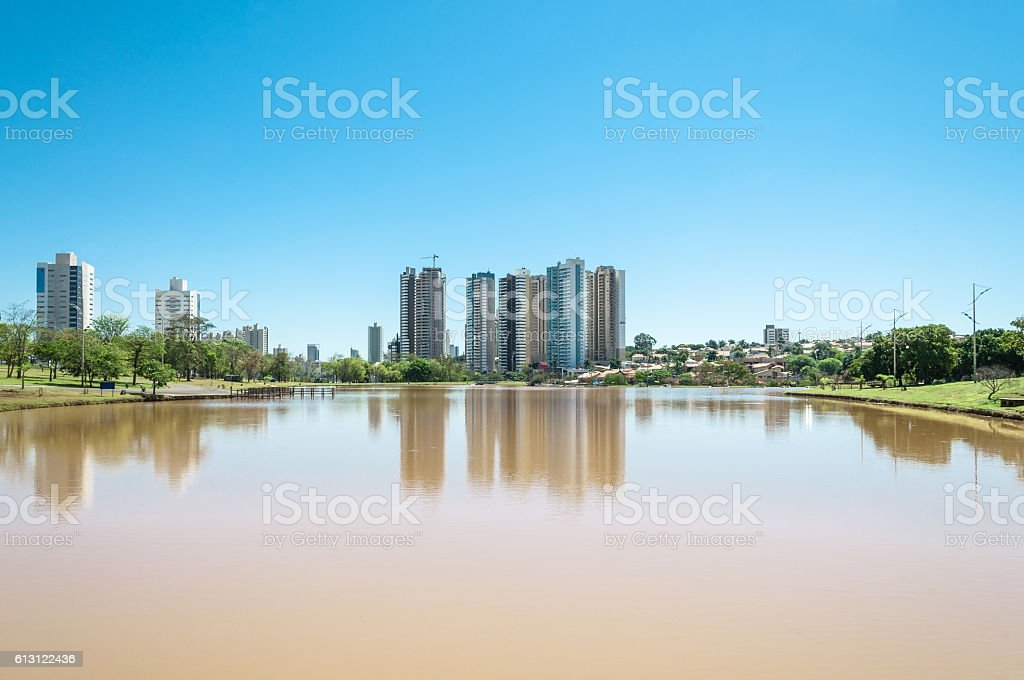 Beautiful sunny day at the lake with city background. stock photo