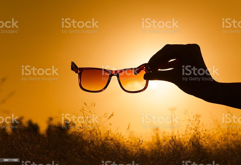 Beautiful sunrise through a pair of sunglasses. stock photo