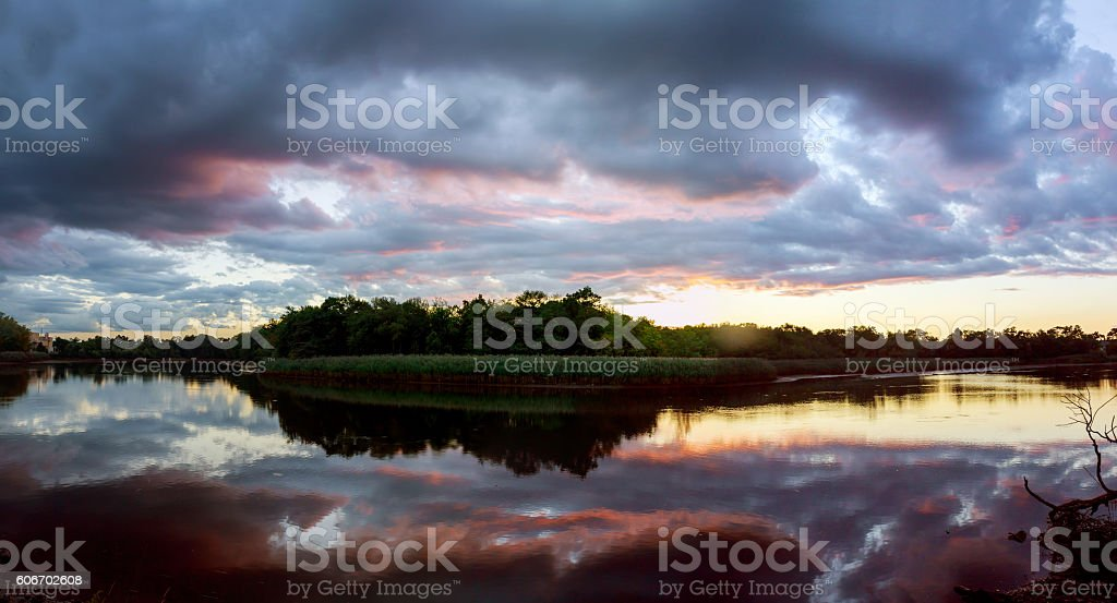 Beautiful sunrise with bright clouds reflected in water stock photo
