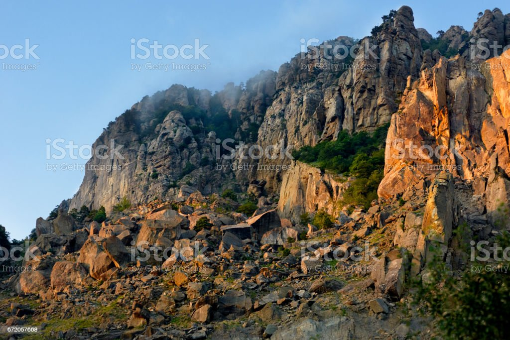 A beautiful sunset in the mountains, a rock lit by the sun. stock photo