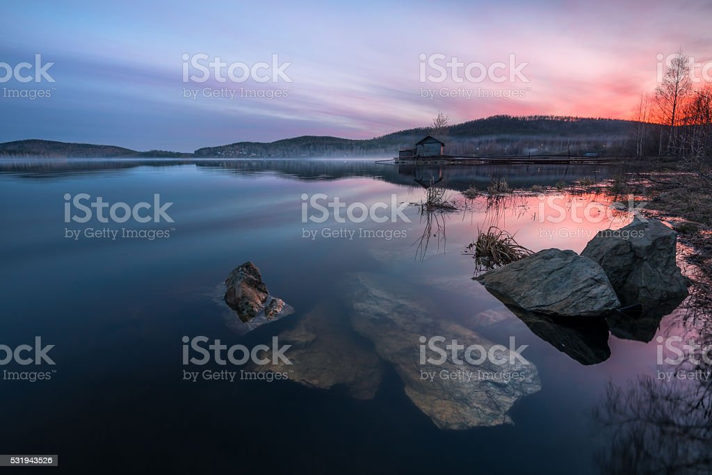 beautiful sunset on the lake with a textured foreground stock photo